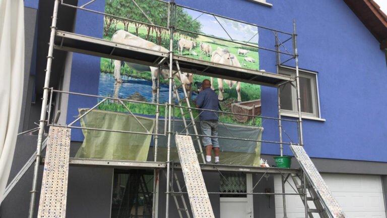 Philippe DEGOTT peint sur le mur d'une maison
